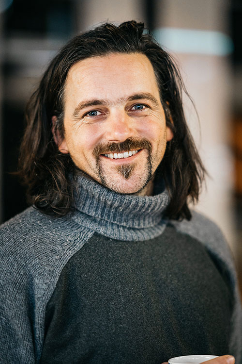 Thor - a medium close-up of a white man with dark hair and a goatee. He wears a grey turtleneck and is smiling.