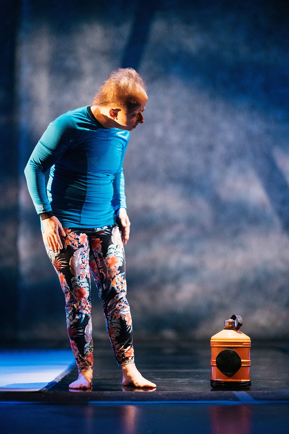 A full portrait shot of a white woman in blue hair standing onstage looking down at an orange water bottle.