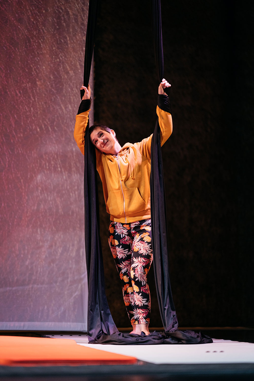 A full portrait shot of a white woman in yellow holding aerial silks in each hand and leaning.