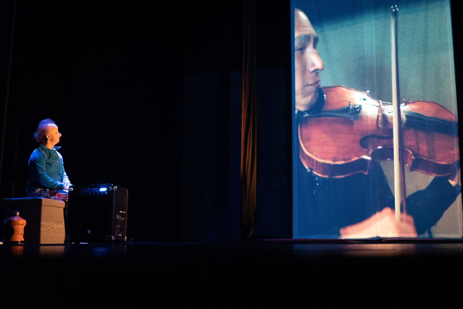 A white woman sits downstage right watching a 14 ft projection of an East Asian man playing the viola.