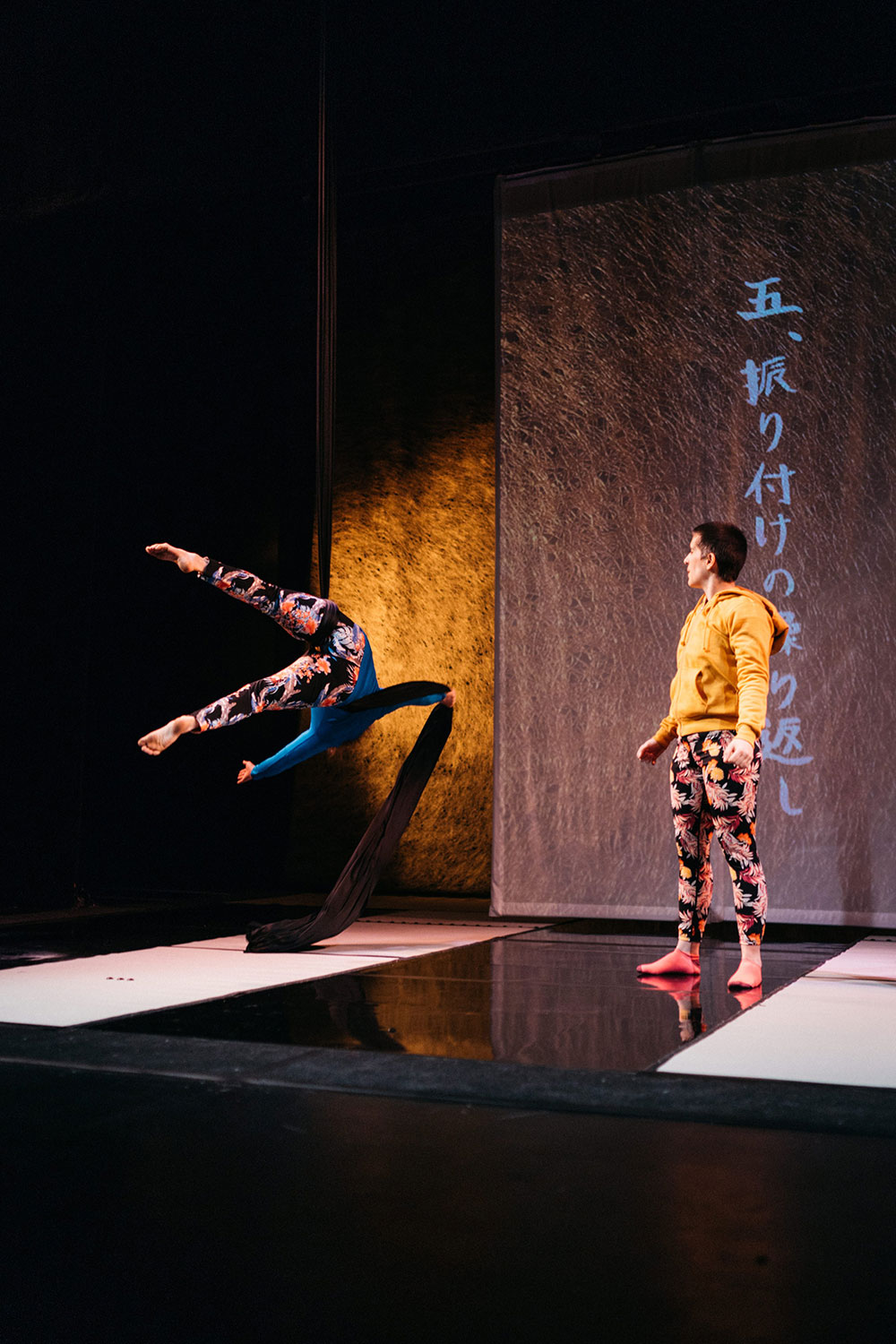 A wide portrait shot of a white woman in blue mid-fall from aerial silks while a white woman in yellow watches.