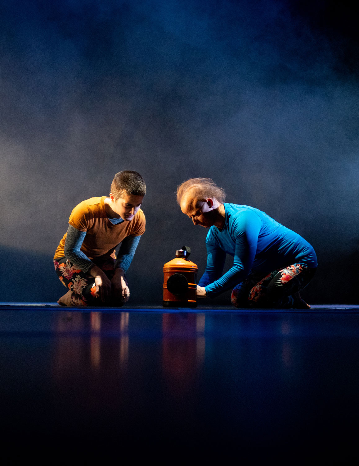 A wide portrait shot of two women crouching onstage either side of a large yellow water bottle.
