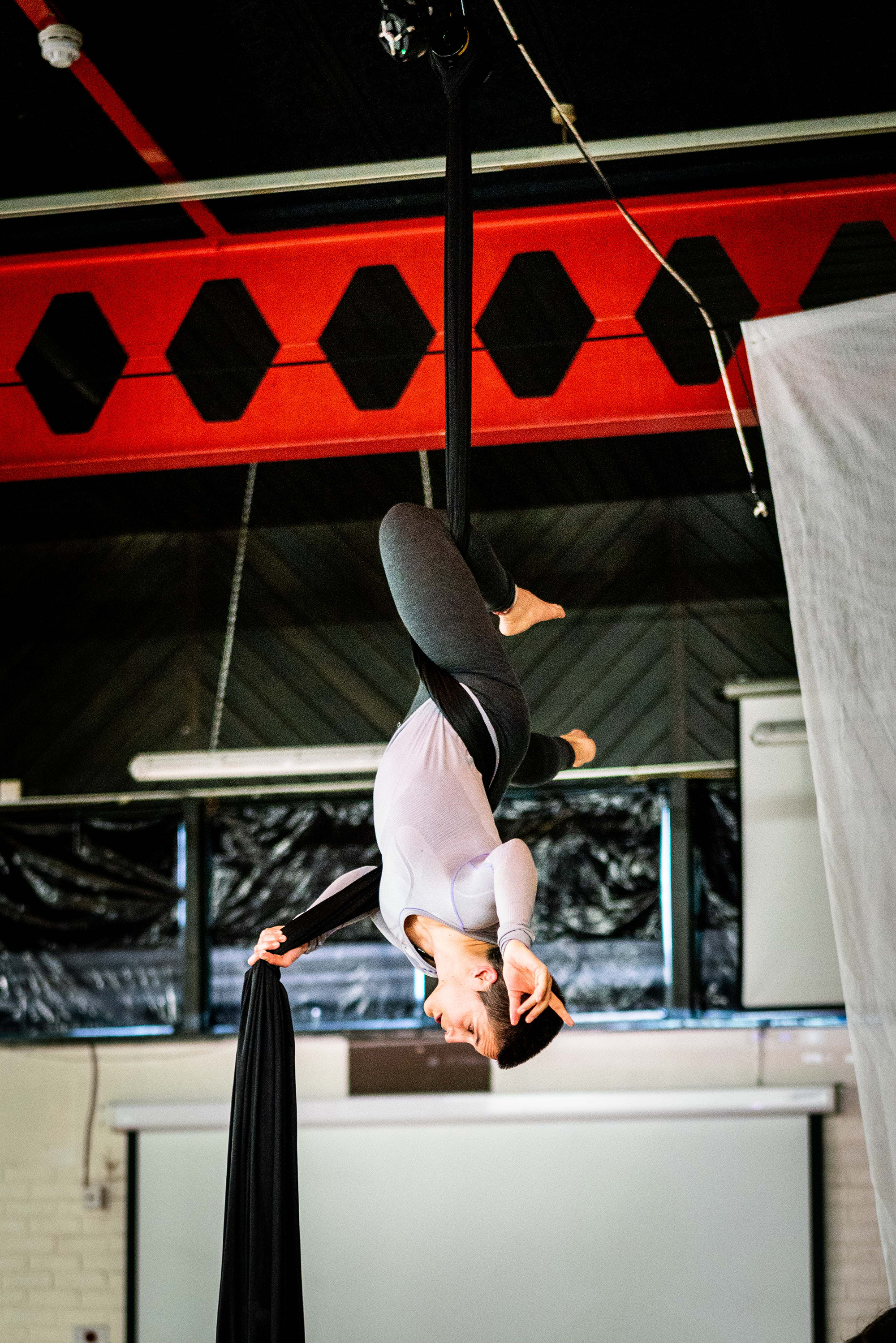 A full shot of a white woman with cropped dark hair hanging upside down from an aerial silk. She looks like she is instructing someone beneath her.
