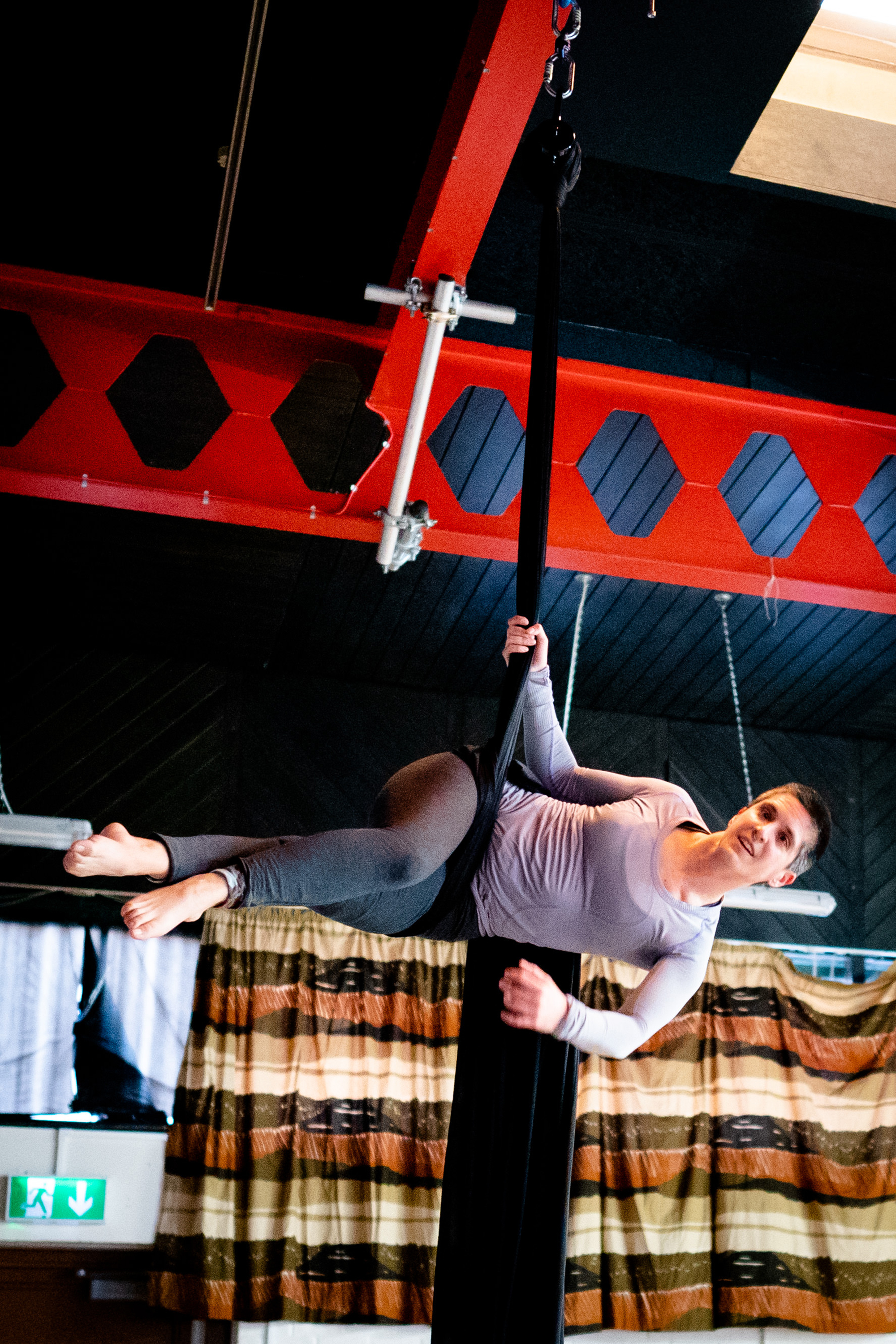 A full shot of a white woman with dark cropped hair suspended horizontally from aerial silks.