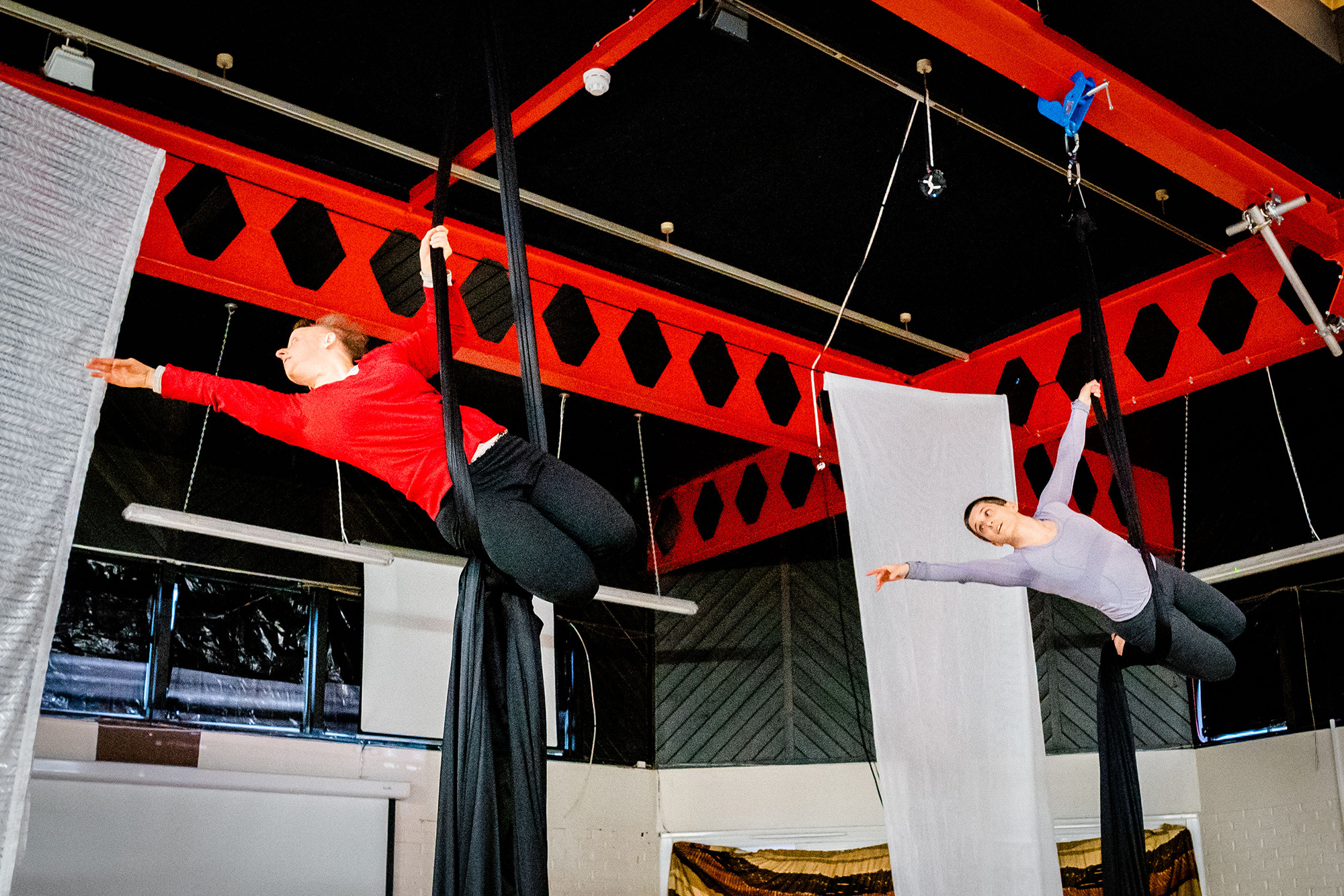 A full shot of two white women 'flying' from right to left suspended from aerial silks