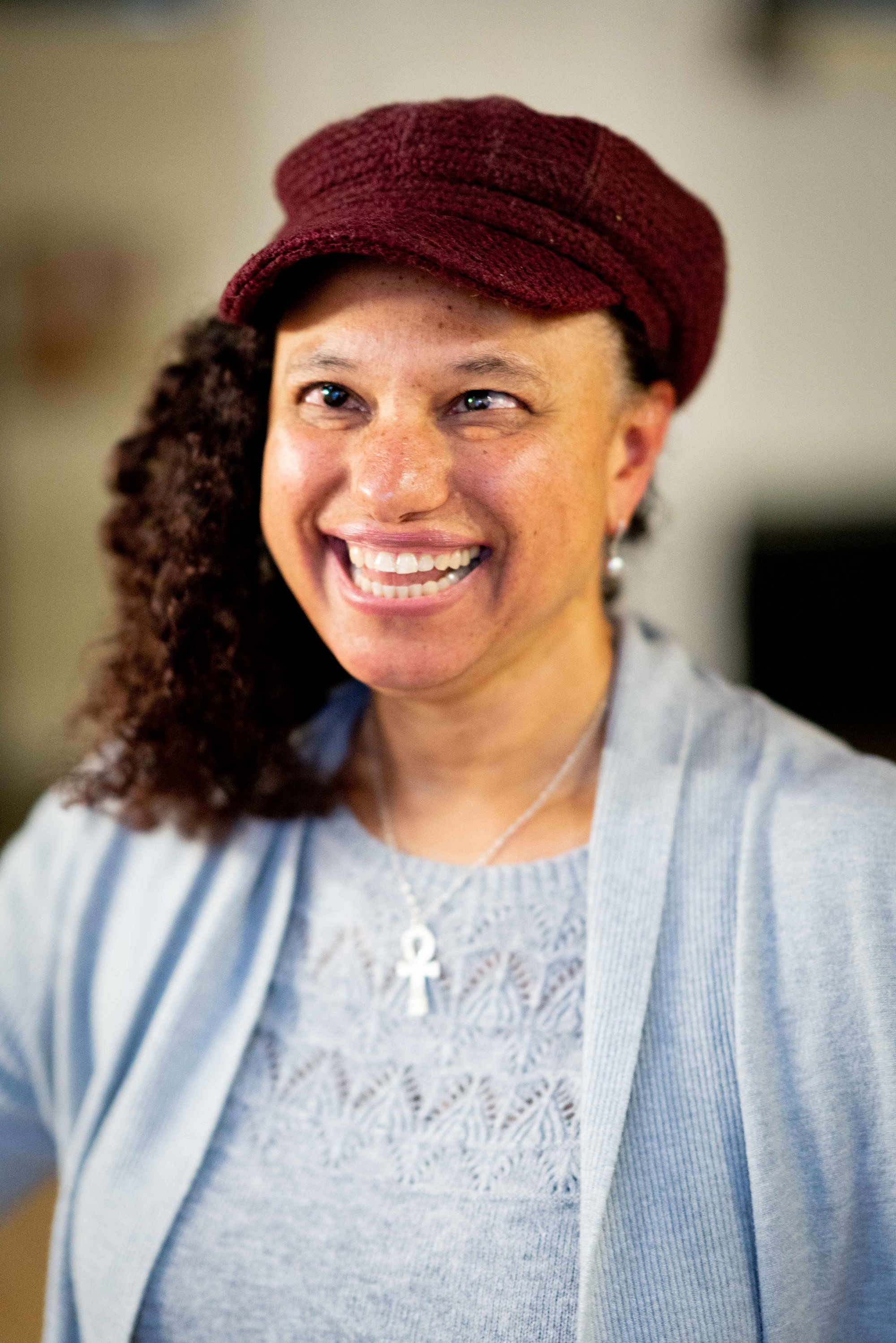A medium close up of a smiling mixed race woman wearing grey. She has a burgundy knitted hat.