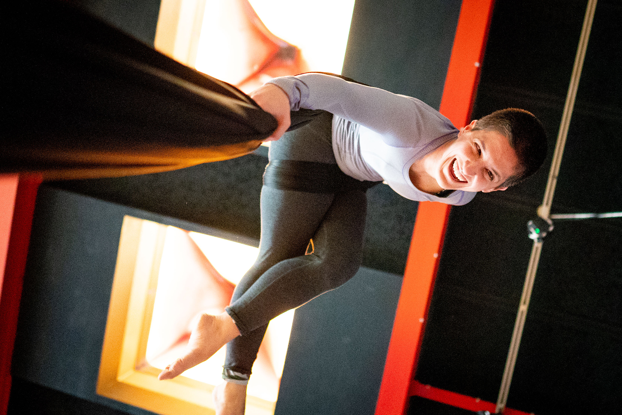 A medium shot from below of a white woman with dark cropped hair suspended from aerial silks and laughing.