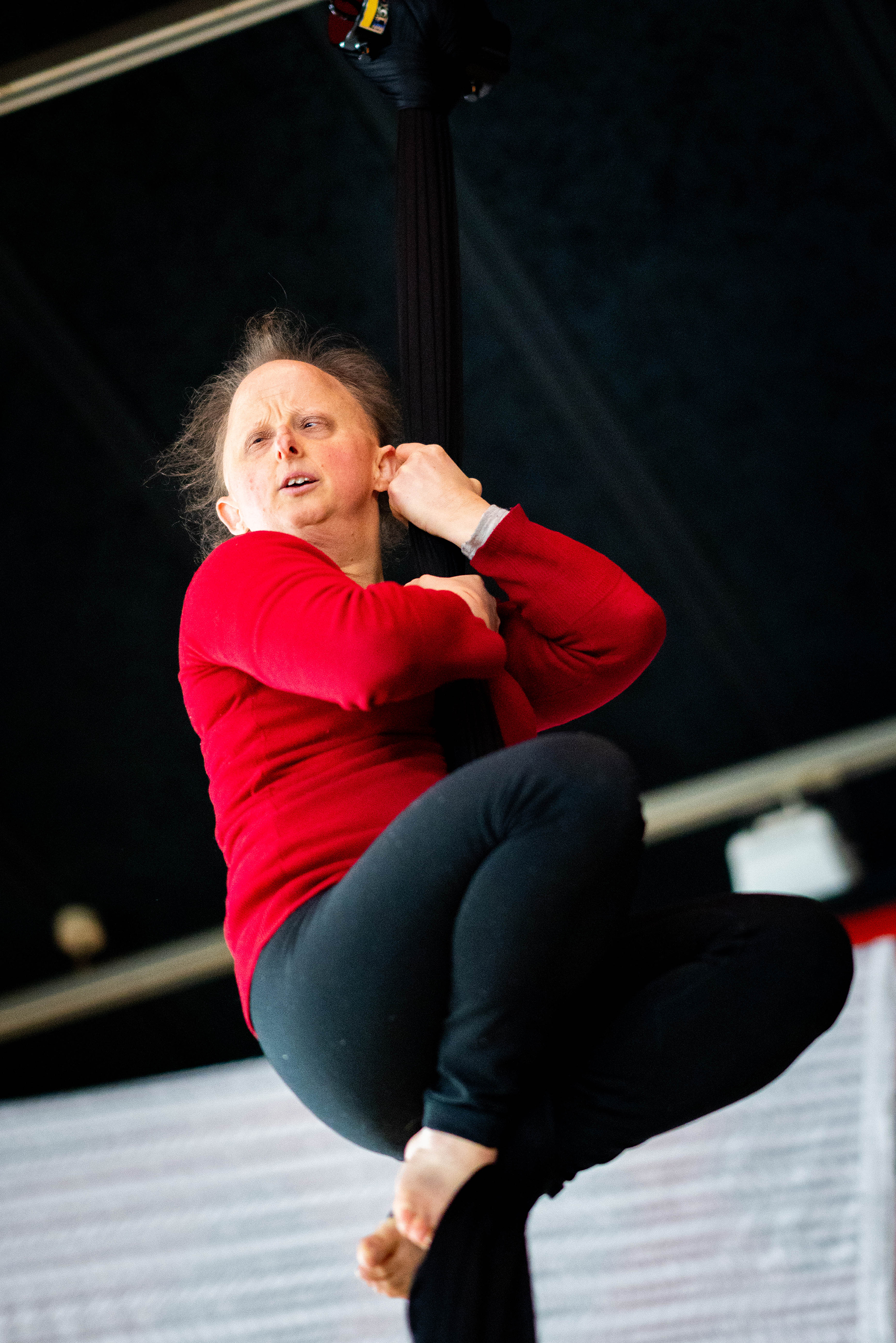 A medium shot of a white woman with thin fair hair clinging to an aerial silks with her hands and feet.