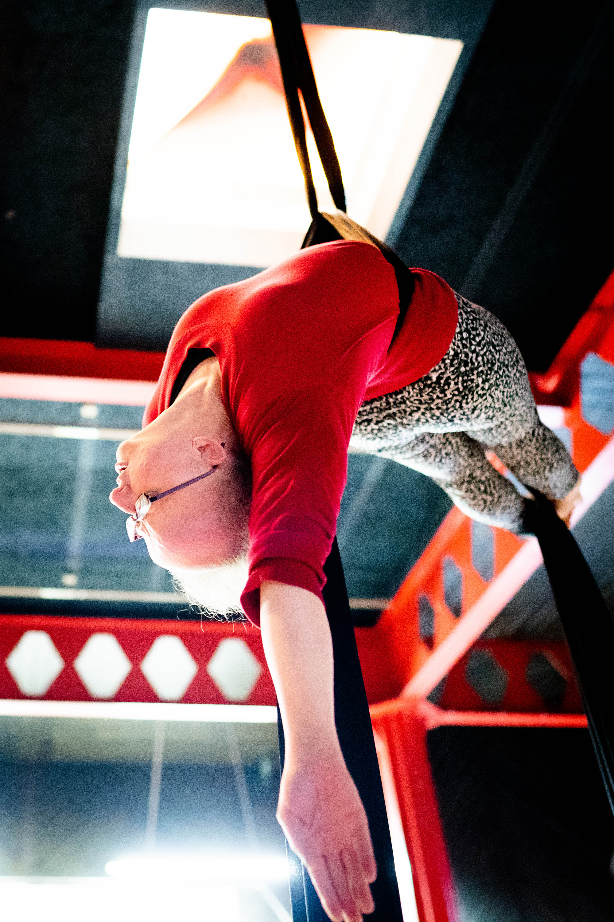 A white woman hangs from an aerial silk, her body forming a horizontal crescent shape in the air. She is photographed from below.
