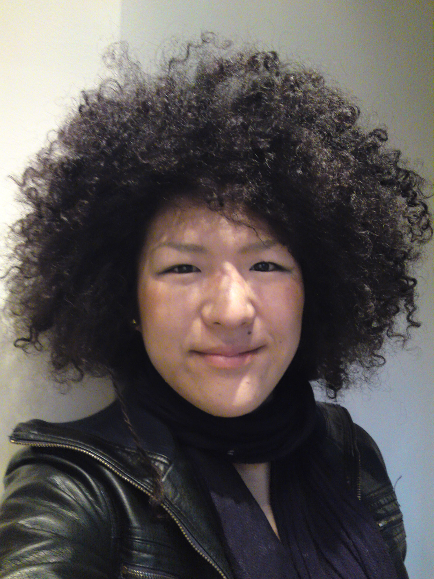 A selfie taken by a woman of East Asian descent with big hair wearing a black scarf and leather jacket.